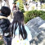 大野川緑陰道路にある中島大水道の石碑にて説明を聞く小学生。